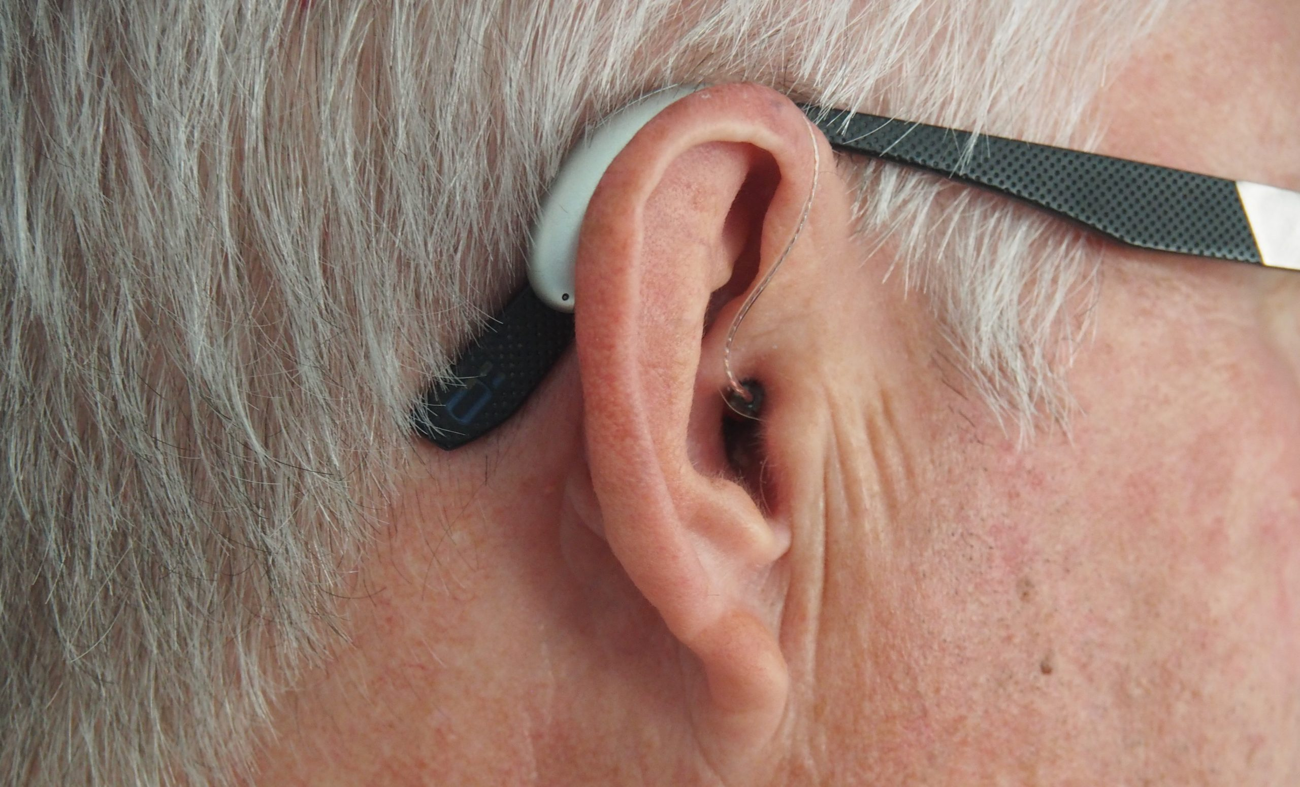 A close up of a man's ear with a hearing aid on.